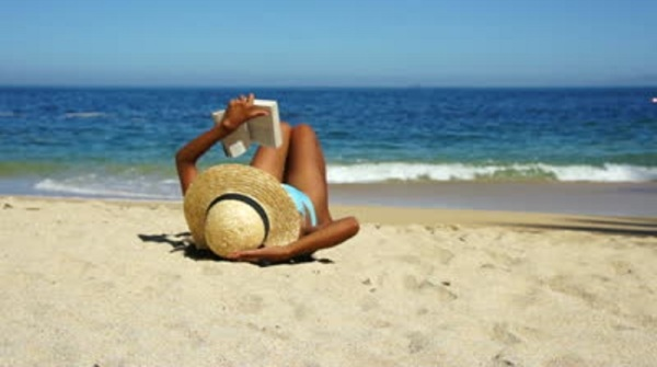 stock-footage-young-women-reading-a-book-at-the-beach-with-waves-in-the-background